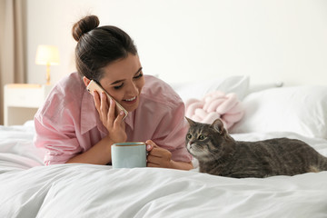 Young woman with cup of coffee talking on phone while lying near cute cat in bedroom. Pet and owner
