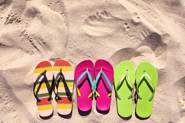 Flat lay composition with flip flops on sand in summer, space for text. Beach accessories