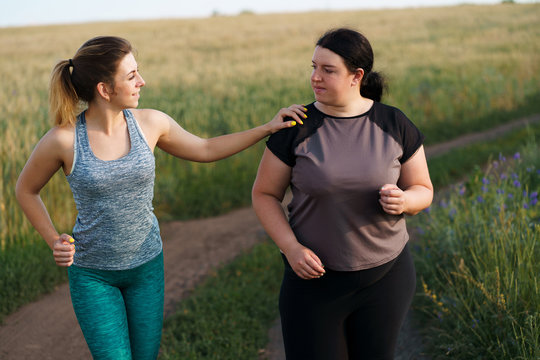 Friendship, personal trainer, group workout, weight loss, sports and health care. Young fit woman support and motivate her overweight female friend at outdoor jogging