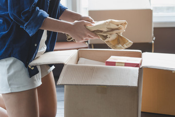 woman unpacking stuff in cardboard box after receive from transportation company and moving to new location apartment.
