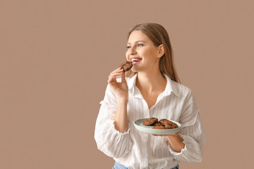 Beautiful young woman with tasty cookies on color background