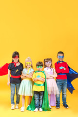 Cute little children dressed as superheroes on color background