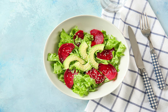 Bowl with tasty beet salad on color background