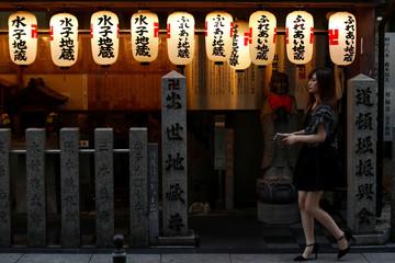 A woman walks past a shrine on a street in Osaka