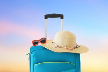 Wall Mural - holidays. travel concept. blue suitcase infront of bokeh background