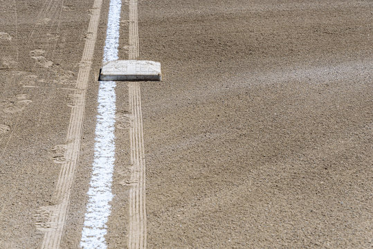 Close up of freshly chalked baseline, with base plate, dirt only, empty baseball field on a sunny day