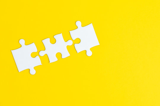 3 jigsaw puzzle on solid yellow background using as 3 important thing combine or working together to success or solve problem