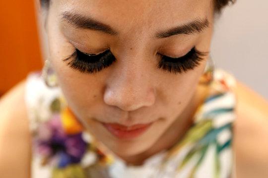 Woman wears fake eyelashes by e-commerce brand Bohktoh in Bangkok