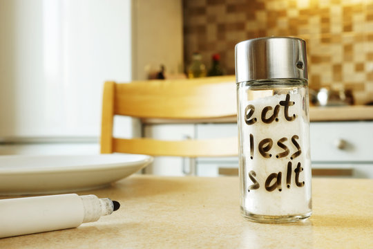 Eat less salt handwritten on glass container.