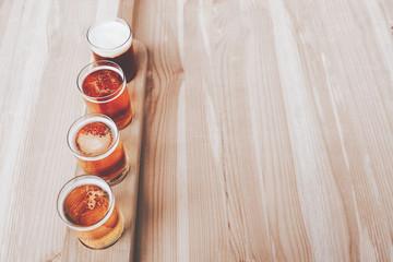 Beer tasting. Diferent beer in 100 mililiter glases over wooden table. Cross-processed. Vintage style. Instagram filter.