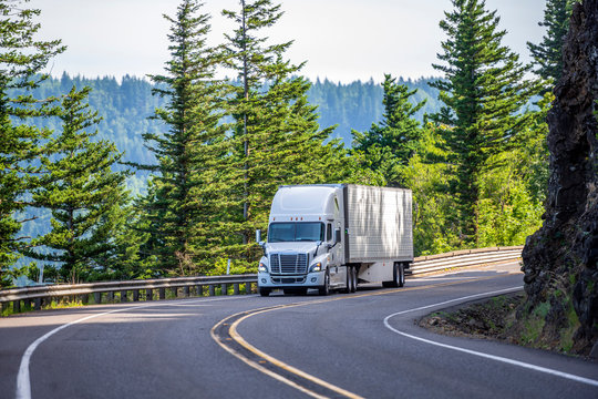 White big rig semi truck transporting goods in refrigerated semi trailer turning on the mountain road with rock wall
