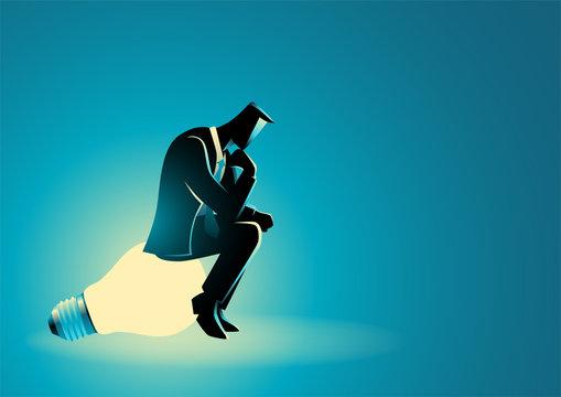 Businessman sitting and thinking on light bulb
