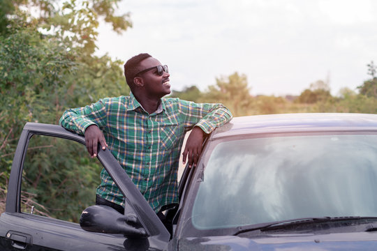 African man standing on the road near opened door of his car.