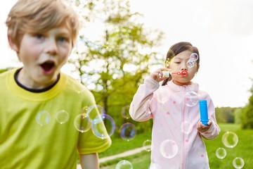 Mädchen macht Seifenblasen auf Kindergeburtstag