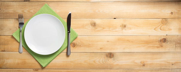 plate, knife and fork at wooden  background