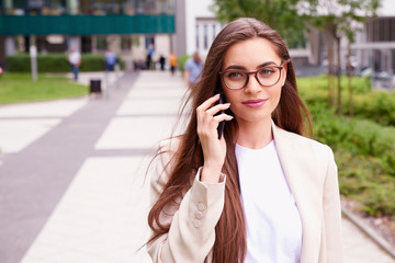 Young businesswoman making a call while walking on the street