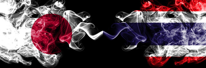 Japan vs Thailand, Thai smoky mystic flags placed side by side. Thick colored silky smokes combination of Thailand, Thai and Japanese flag