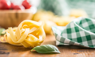Italian pasta tagliatelle on table with basil and tomatoes