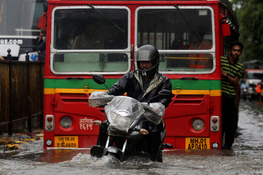 A man rides a motorcycle through a water-logged street during heavy rains in Mumbai