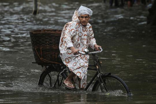 A man rides a bike through a water-logged street during heavy rains in Mumbai