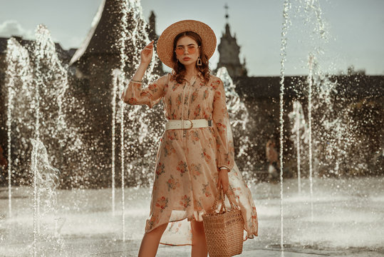 Outdoor portrait of young fashionable woman wearing straw hat, pink sunglasses, stylish dress with leather belt, holding straw wicker basket bag, posing in street of European city. Copy, empty space