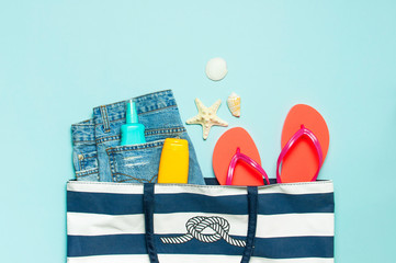 Wall Mural - Summer sea accessories. Beach bag Coral flip flops denim shorts shells starfish sunscreen bottle body spray on blue background top view flat lay. Summer background. Holiday vacation travel concept