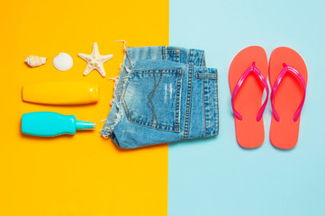 Wall Mural - Summer beach sea accessories. Coral flip flops denim shorts shells starfish sunscreen bottle body spray on blue yellow background top view flat lay. Summer background. Holiday vacation travel concept