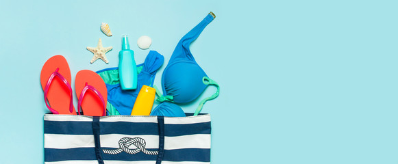 Wall Mural - Summer sea accessories. Beach bag Coral flip flops swimsuit shells starfish sunscreen bottle body spray on blue background top view flat lay. Summer background. Holiday vacation travel concept