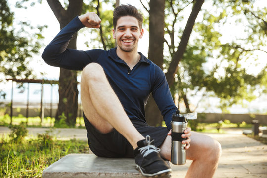 Portrait of strong athletic man sitting on bench and showing his bicep while doing workout in sunny green park