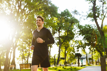 Portrait of joyful athletic man running while doing workout in sunny green park