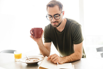 Happy young bearded man wearing eyeglasses indoors at the kitchen have a breakfast eat corn flakes with milk reading book drinking coffee.