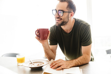 Smiling young bearded man wearing eyeglasses indoors at the kitchen have a breakfast eat corn flakes with milk reading book drinking coffee.