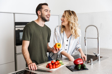 Happy young loving couple indoors at the kitchen cooking vegetable salad have a breakfast.