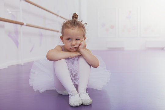 Adorable little girl ballerina looking grumpy, sitting alone on the floor at ballet school, copy space. Cute little ballerina looking bored and annoyed at ballet dancing class