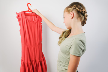 Teen girl choosing a dress for a fitting standing over grey background. Caucasian girl holding a...