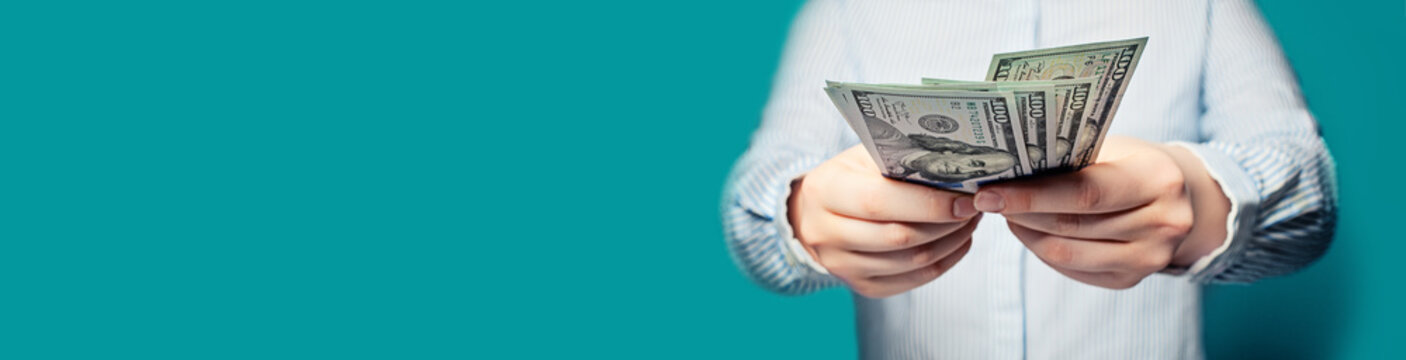 Hands with money US dollars on blue background banner