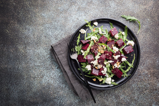 beetroot salad with blue cheese, arugula and walnut in a black plate on stone background, top view