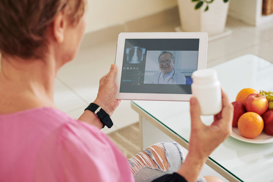 Elderly woman video calling her physician and discussing tablets and pills with her doctor