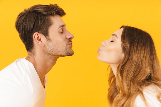 Portrait closeup in profile of caucasian couple man and woman kissing each other with eyes closed while standing face to face