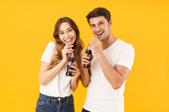 Portrait of content couple man and woman in basic t-shirts standing together while drinking soda beverage with straws