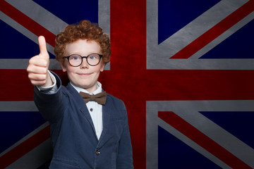 Happy young boy student on the UK flag background. Learn English language