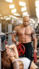 Muscular man helping athletic woman with lifting exercise vertical position of the picture, convenient for use on a smartphone, the effect of sun glare