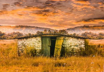 Stone barn building in the grass field at sunset. Abandoned old shed in fairy tale scene. Styled stock photo with the countryside in Romania.