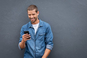 Cool smiling man using smartphone on grey wall
