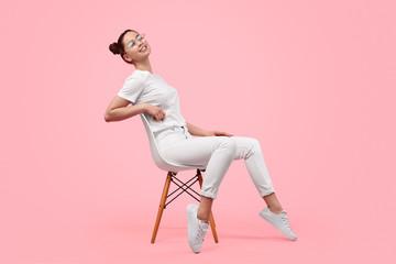 Fototapeta Relaxed teen girl sitting on chair
