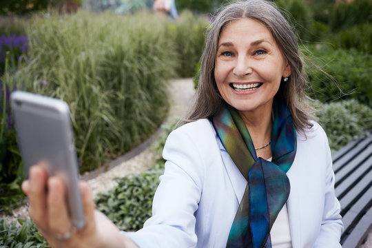 Outdoor shot of cheerful attractive sixty year old lady in stylish clothes smiling broadly keeping arm outstretched holding mobile phone taking self portrait against amazing nature background