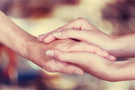 Hands of the old man and a young woman. close up.