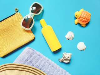 Sunny flat lay beach photo. Yellow cosmetic bag, sunglasses, sunscreen, seashells, towel and rubber...