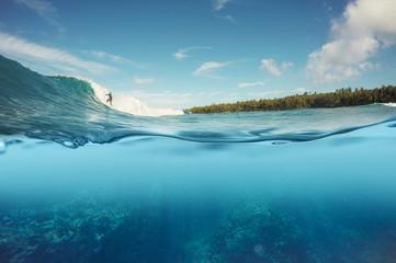 half underwater shot of surfer surfing a wave
