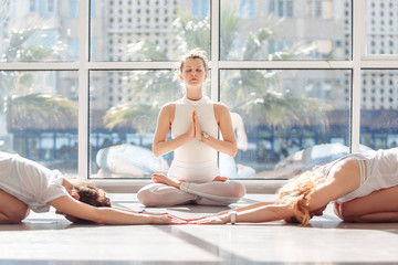 Group yoga classes young woman meditating in lotus position next to two female students doing balasana lying on floor in gym. Concept of group classes and stretching, white light sport hall, sportwear